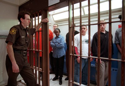 Oakland County deputy Joe Groome stands guard as students from Pontiac Northern, Central and Clarkston  High School peer through the bars of a jail cell during their student tour of the Oakland County jail.