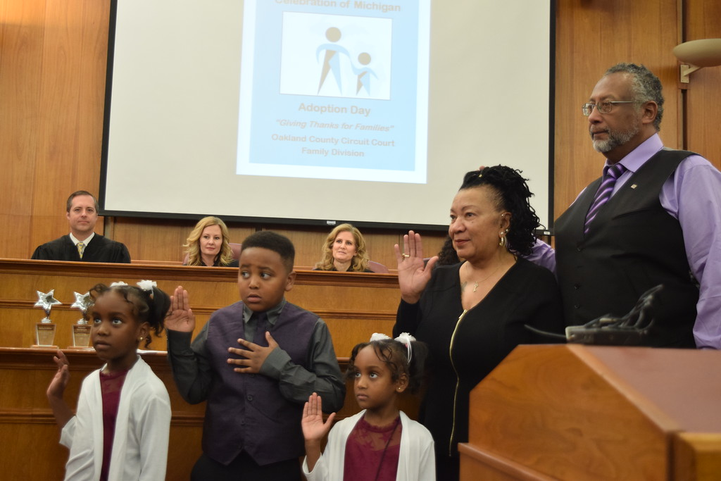 . Ricardo Russell (right) stands with his wife Clara as they finalize the adoption of Daniel, Clara and Aliana. Seven adoptions were finalized at the Oakland County Board of Commissioners Auditorium, 1200 N. Telegraph Road, Pontiac, Mich., on Tuesday, Nov. 21, 2017 as part of Michigan Adoption Day. Over 30 other courts around the state held their own finalization ceremonies. (Mark Cavitt/The Oakland Press)