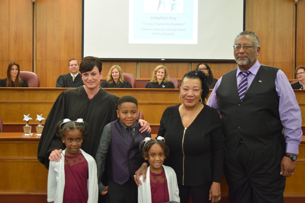 . The Russell Family stands with Family Division Presiding Judge Lisa Gorcyca. Seven adoptions were finalized at the Oakland County Board of Commissioners Auditorium, 1200 N. Telegraph Road, Pontiac, Mich., on Tuesday, Nov. 21, 2017 as part of Michigan Adoption Day. Over 30 other courts around the state held their own finalization ceremonies. (Mark Cavitt/The Oakland Press)