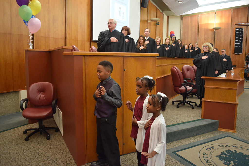 . Daniel Russell stands with his sisters Clara and Aliana during the Pledge of Allegiance. All three were adopted on Tuesday  at the Oakland County Board of Commissioners Auditorium, 1200 N. Telegraph Road, Pontiac, Mich., as part of Michigan Adoption Day. Over 30 other courts around the state held their own finalization ceremonies. (Mark Cavitt/The Oakland Press)