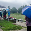 Spectators huddle up in the rain during the Fast Break summer league game on Tuesday afternoon. SENTINEL & ENTERPRISE / Ashley Green