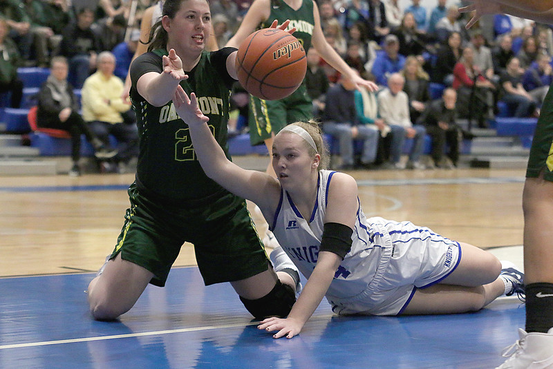 Lunenburg Middle High School girls basketball team played a home game against Oakmont Regional High School on Tuesday afternoon. ORHS player Kylie Lison makes a pass from her knees as LMHS player Sarah Blomgren tries to stop her after they fought for a loose ball. SENTINEL & ENTERPRISE/JOHN LOVE