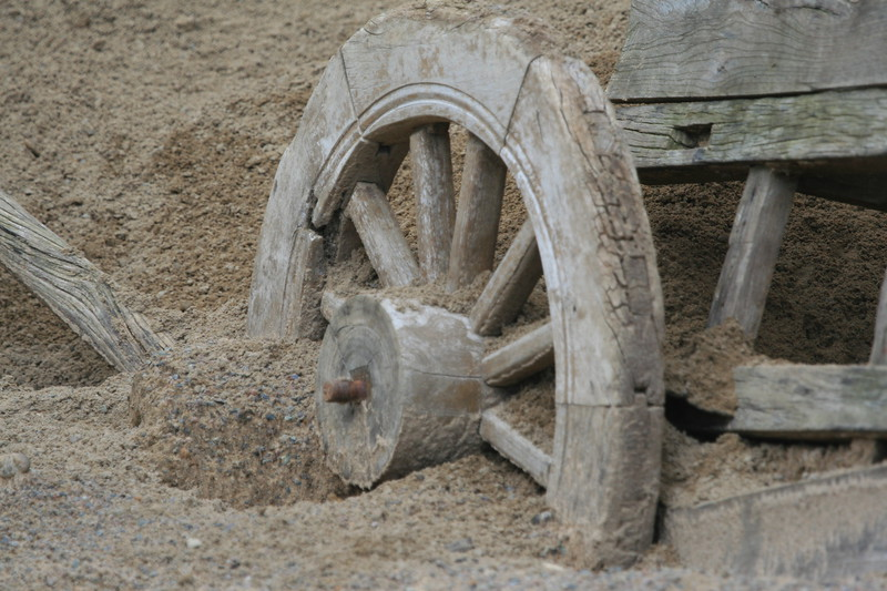Old wooden cart replica from 4 B.C. era shown stuck in the sand.