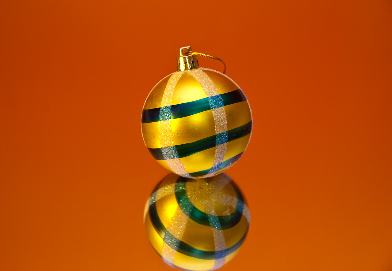 Striped yellow ball on a mirror