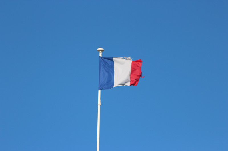 French Flag, damaged, flying above Antibes, France