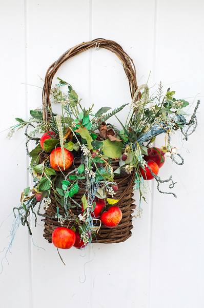 A basket of flowers and fruit on a white door in Essex, Connecticut.