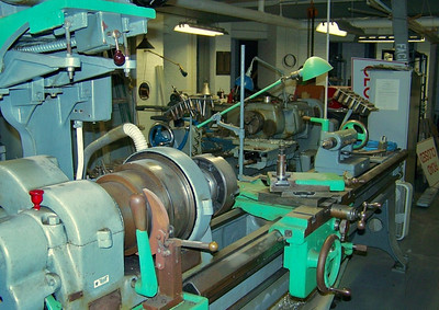 This lathe is unmarked, but it is the largest one in the shop. Must have about 5 ft between centers. The paint has worn off in spots on the cross slides and apron, and various knobs and thus was repainted. The ways are beautiful for this antique machine!