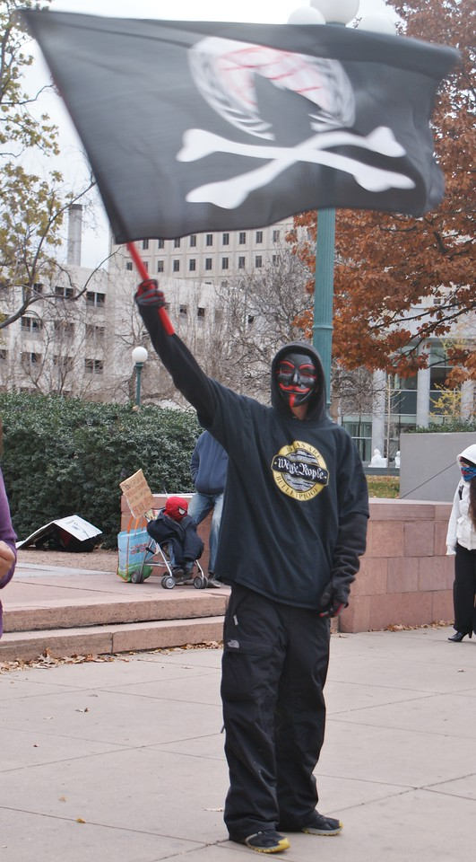 """Protester at the Million Mask March in Denver, displays the """"anonymous"""" flag."""