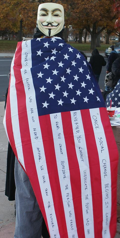 "Masked protester displays American flag at ""Million Mask March"" in Denver."
