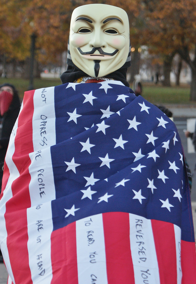 "Masked protester displays American flag at ""Million Mask March"" in Denver."