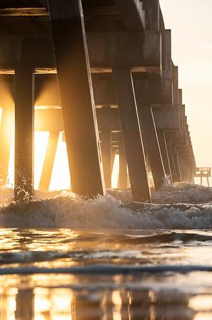 Sunrise Light through Pier Pilings.