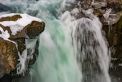 Icicles and Snow on Boulders at Small Waterfall
