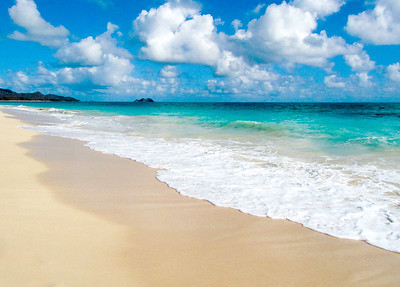 """Waimanalo Beach has some of the most beautiful bright turquoise water, and powdery soft, white sand.  The Mokapu Peninsula and the Mokulua (or """"the Mokes"""") Islands seen in the distance Windward Oahu, Hawaii"""