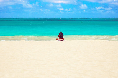 Girl sitting on the soft powdery white sand of Waimanalo Beach