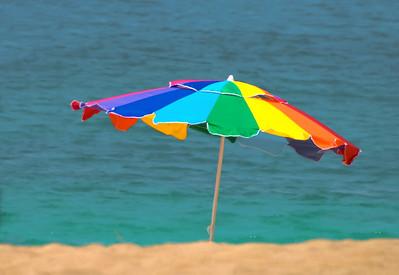 Sunset Beach Rainbow colored umbrella in the sandNorth Shore, O'ahu, Hawai'i  September, 2008