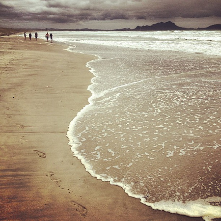 A walk on the beach, footprints track the water's edge -- Uretiti, North Island, New Zealand
