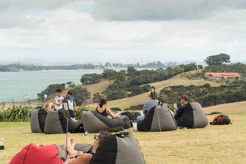 People enjoying the view of Auckland from the lawn of the Cable Bay Vineyard.