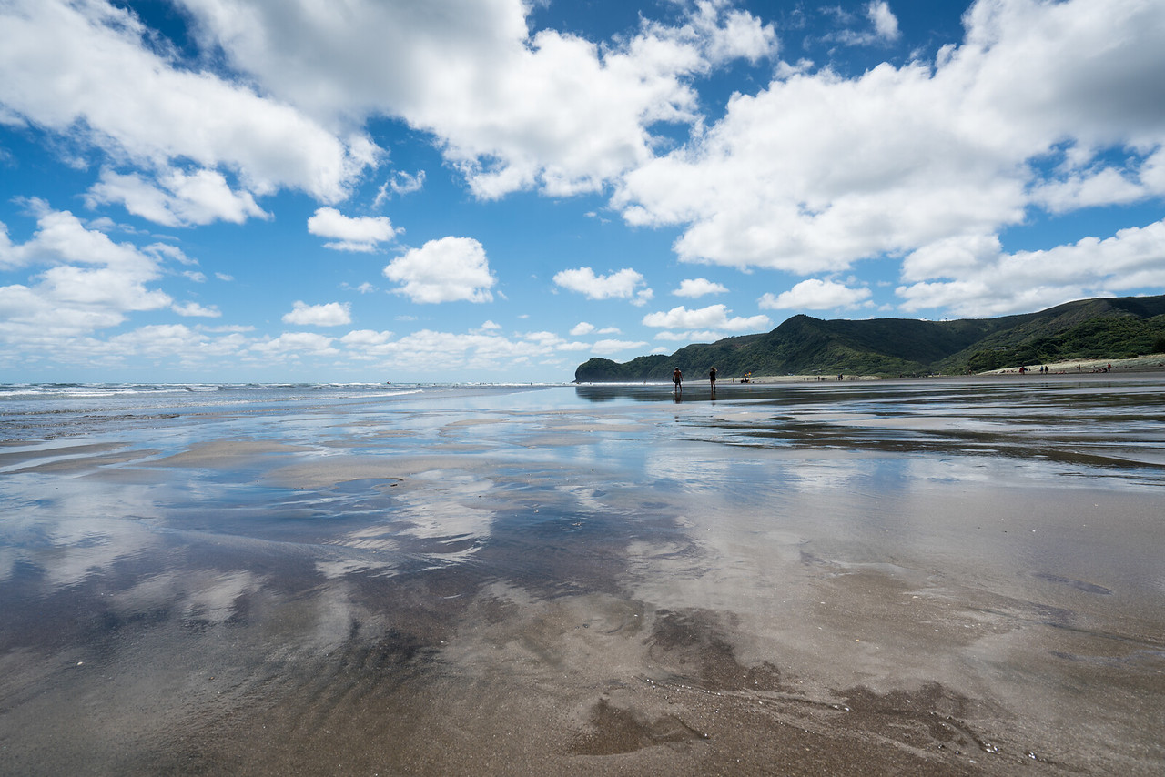 Clowds reflected in the wet sand, Piha Beach.