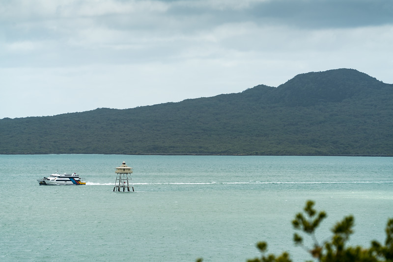 A ferry passes a light marking a shoal. Rangitoto in the background.