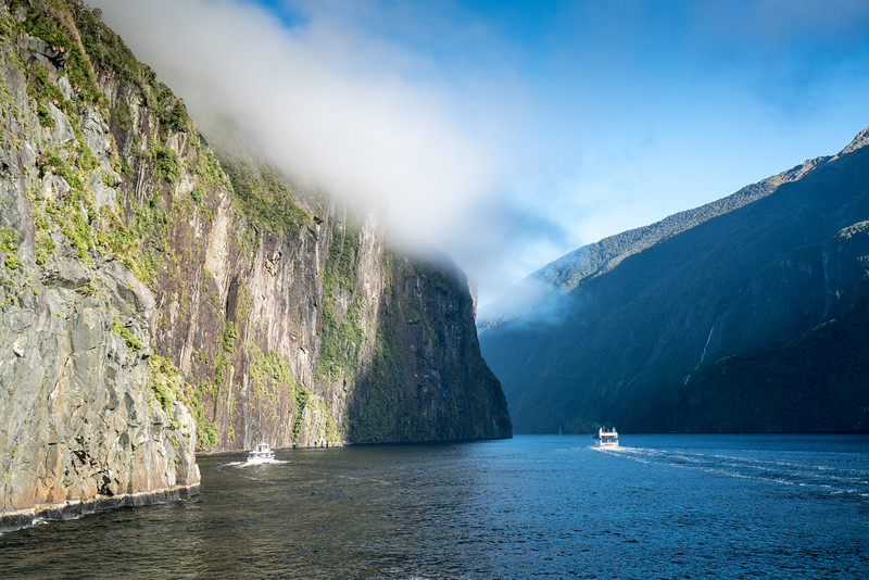 A couple of other boats cruising the sound as clouds spill over the top of the fjord.