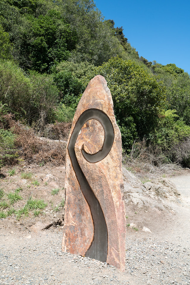 Upright stone with Maori symbol.