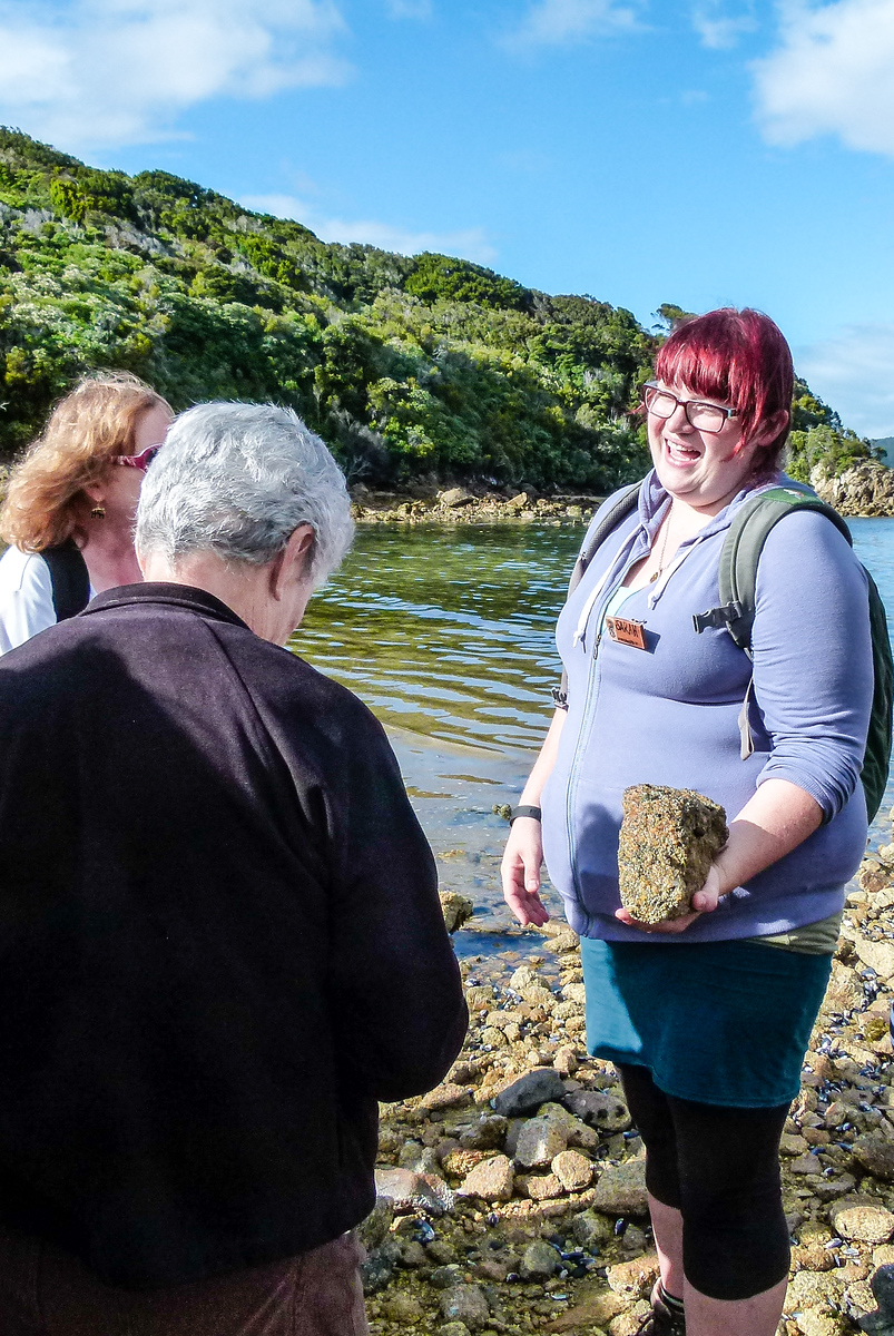 A guide on Ulva Island holds a rock as she lectures about geology.
