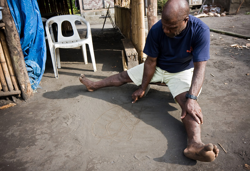 Philip, chief of Emiotungun village, demonstrates for me the Ambrym island art of sand drawing.<br /> <br /> Location: Ambrym island, Vanuatu<br /> <br /> Lens used: 17-55mm f2.8 IS