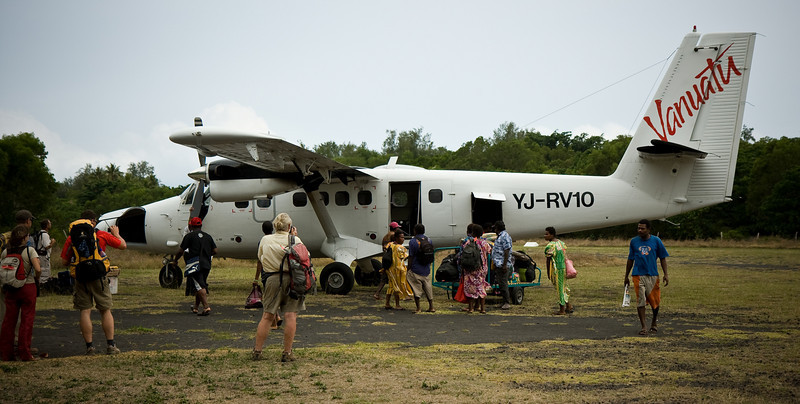 A crowd of tourists and locals alike wait to board Air Vanuatu's Twin Otter at Craig Cove.<br /> <br /> Location: Ambrym island, Vanuatu<br /> <br /> Lens used: 17-55mm f2.8 IS