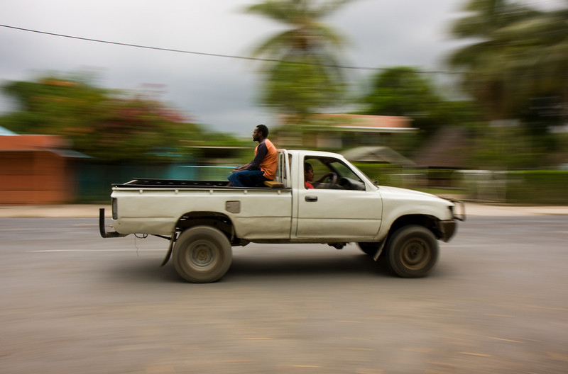Transport trucks such as this make up the primary method of road transport around those islands that have roads - piling in the back with others can be a social affair.  Here, a lone rider keeps himself company.<br /> <br /> Location: Downtown Luganville, Santo island, Vanuatu<br /> <br /> Lens used: 17-55mm f2.8 IS