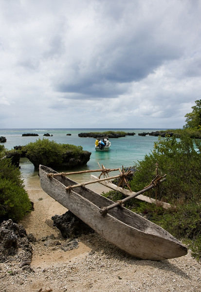 Boats, old-style and new- pulled up on a thin strip of beach along the island's rocky  west coast.<br /> <br /> Location: Tanna island, Vanuatu<br /> <br /> Lens used: 17-55mm f2.8 IS