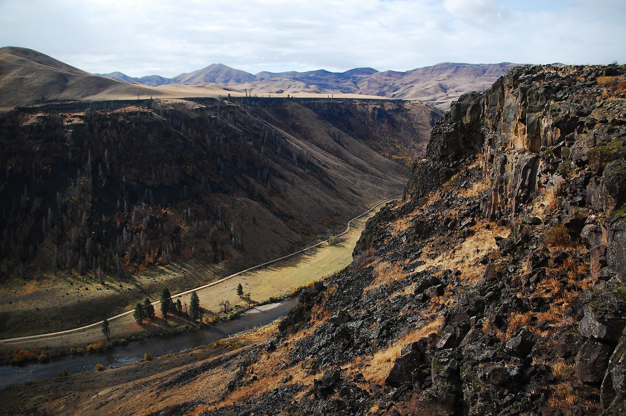 """Prairie Road along the S F Boise River, black rock outcroppings on either side.  It's amazing to consider the geological forces that wore away this rock.  Like Red observed in 'Shawshank Redemption': """"Pressure...and time...""""."""