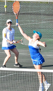 KYLE MENNIG - ONEIDA DAILY DISPATCH Cazenovia's Laura Connor hits the ball at the net as her sister and teammate Lucy Connor looks on during a first doubles match against Oneida in the Section III Class B final in Utica on Friday, Oct. 7, 2016.