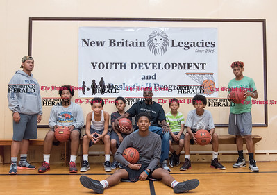 101016   Wesley Bunnell | Staff  Deivone Tanksley Sr. ,seated middle, sitting with team members from a new basketball league he has fired named New Britain Legacies in the gym at St. Matthew on Monday afternoon.