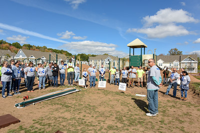 101216  Wesley Bunnell | Staff  The Simon Konover Company held a playground community building project at Industria Commons housing community on Wednesday with the help of company volunteers.  Konover President Jim Wakim , right, addresses the approximately 60 volunteers.