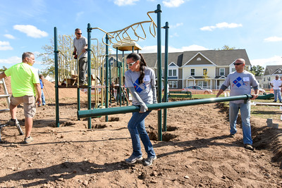 101216  Wesley Bunnell | Staff  The Simon Konover Company held a playground community building project at Industria Commons housing community on Wednesday with over 60 volunteers from the company. Volunteers move pieces into place.
