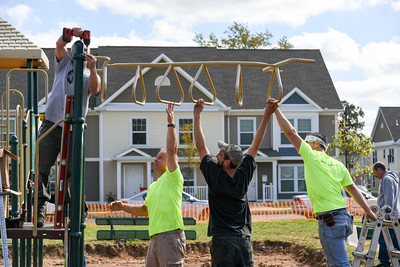 101216  Wesley Bunnell | Staff  The Simon Konover Company held a playground community building project at Industria Commons housing community on Wednesday with the help of company volunteers.  Volunteers hold up pieces of a monkey bars while being attached.