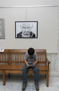 "101216  Wesley Bunnell | Staff  Mayor Erin Stewart and the Commission on the Arts held a reception Wednesday evening at City Hall titled ""Leading by Example: Works by New Britain Public School Art Teachers"". Fourteen teachers from across the district have work on display until Nov 25. Skyler Knapp whose mother has work on display sits under a sketch titled The Heisenberg Stare by Joel Corriveau from Slade Middle School."