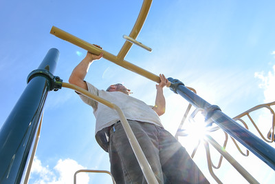 101216  Wesley Bunnell | Staff  The Simon Konover Company held a playground community building project at Industria Commons housing community on Wednesday with the help of company volunteers.  Looking up as a volunteer guides the installation of monkey bars into place.