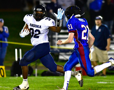 10/13/2016 Mike Orazzi | Staff St. Paul Catholic High School's Damien Rabis (21) and Ansonia's Malcolm Martin (32) in Bristol Thursday night.