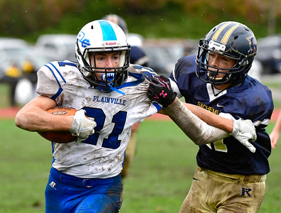 10/22/2016 Mike Orazzi | Staff Plainville's Jake Theriault (21) and RHAM's Sam Macmillan (11) in Hebron Saturday.