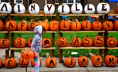 10/22/2016 Mike Orazzi | Staff Lila Cassinari walks past pumpkins on display during the 2nd annual Plainville PumpkinFest Saturday.