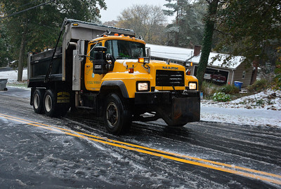 10/27/2016 Mike Orazzi | Staff A public works truck spreads sand on a slick Woodland Street during Thursday's snowstorm.