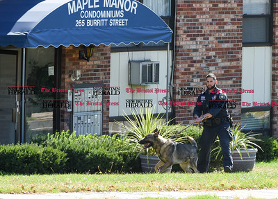 100516  Wesley Bunnell | Staff  New Britain Police Ofc. Rejean Ouellette with his K-9 Pup just before the suspect was led from 265 Burritt St on Wednesday afternoon after a hours long stand off with police.
