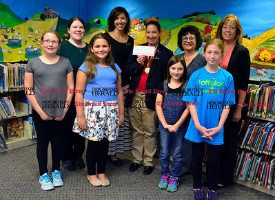 10/5/2016 Mike Orazzi | Staff Special Olympics representative Angie D'Amico holds a $500 check received from UBI Federal Credit Union through the Plainville Public Library. Left to right: Emily Crombie, Jessica Nelson, Gianna Fiordellisi,  Ericka Bajrami, D'Amico, Lily Fogg, Pat Amato, Avery Verrastro and Sharon Rozum.