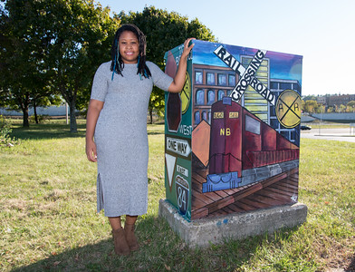 100616  Wesley Bunnell | Staff  Local artist Kayla Farrell , a member of the New Britain Artists' Co-Op poses with her work located on East Main St. The theme of the high voltage box art work is New Britain Past & Present Transportation.
