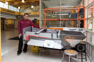 100716  Wesley Bunnell   Staff  E.C. Goodwin Technical High School Senior William Diaz poses with a boat he helped design on Friday afternoon. The boat which was built of cardboard and duct tape placed 5th in a contest of 26 schools in an event sponsored by UCONN Avery Point.