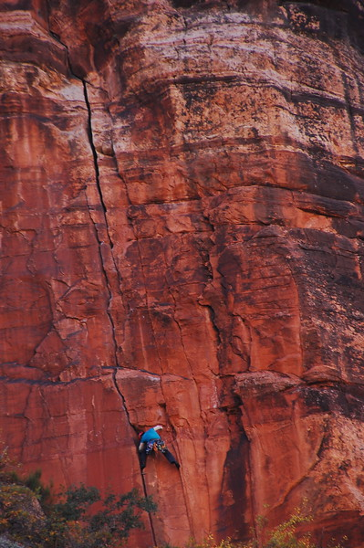Rock climber working his way up a vertical cliff face at Zion NP.