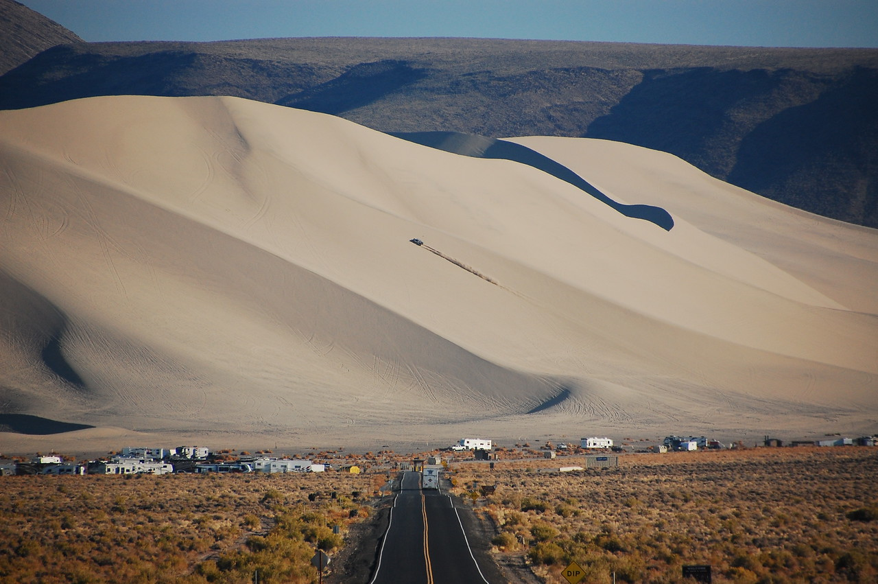 "Coming into Nevada on US Rt 50 is ""Sand Mountain"", a massive sand dune that has become a sort of ATV playground.  Here's the road in to Sand Mountain, with RVs and toy haulers clustered at its base.  A lone Razor hammers it up the side of the dune, spewing sand in its wake."