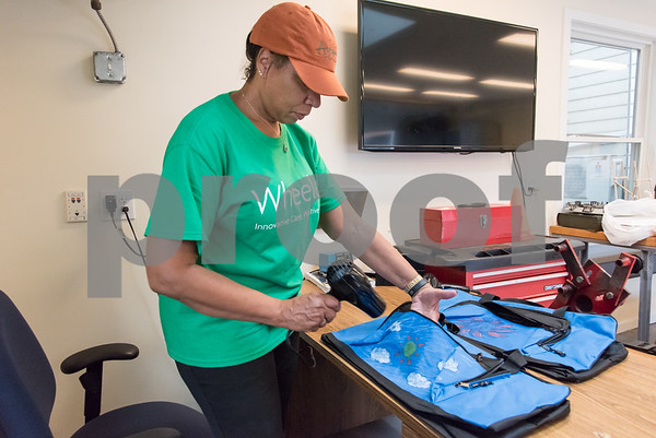 10/09/17 Wesley Bunnell | Staff Volunteers from the Mott Corporation donated their time and items to stuff duffle bags for kids in Wheeler Clinic's foster care program. Wheeler Clinic employee Rhoda Franklin uses a dryer to help set the designs into the fabric with the help of a hair dryer.