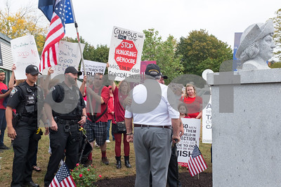 A ceremony was held on Monday morning at the Southington Municipal Center for the dedication and unveiling of the Christopher Columbus Monument honoring the 525th anniversary of the discovery of America. A veteran speaks to a protestor who is holding the American flag upside down.